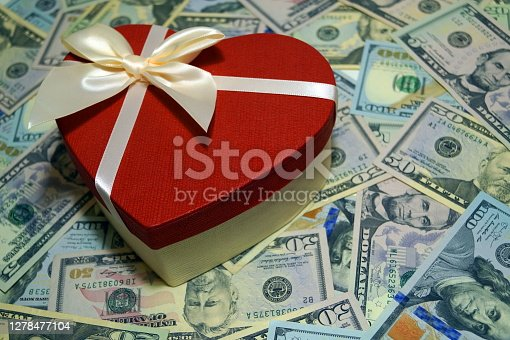 A red gift in the form of a heart with a beige ribbon lies on a lot of US dollars. Valentine's Day, Holiday.