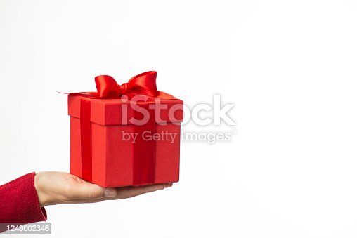 Woman giving red gift box against white background.