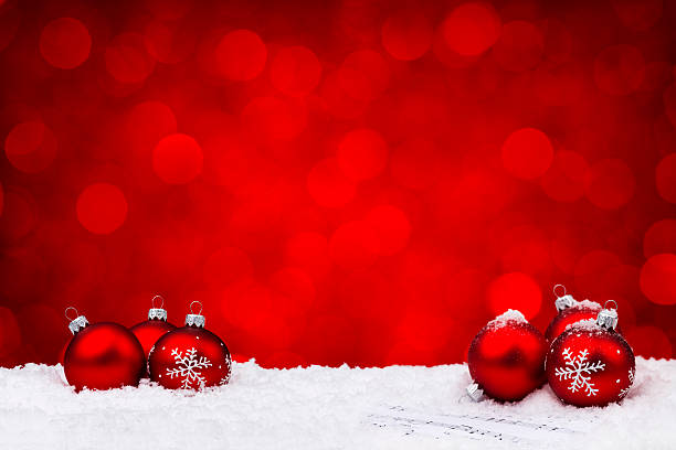 Red glass ornaments on sheet music with red background stock photo