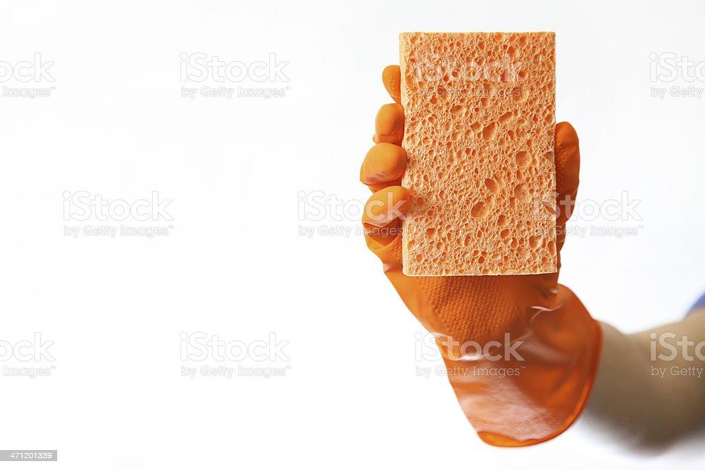 red glove holds up orange sponge against white background royalty-free stock photo
