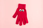 red  glove  with googly eyes isolated  on a pink background