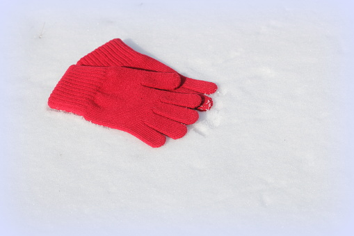 Red gloves on white snow background .