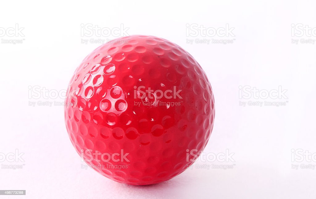 red golf ball on red tee, white background stock photo