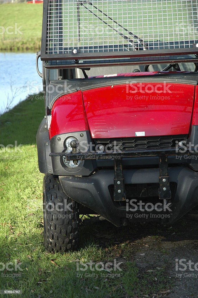 Red golf car (cart) detail parked next to the water royalty-free stock photo