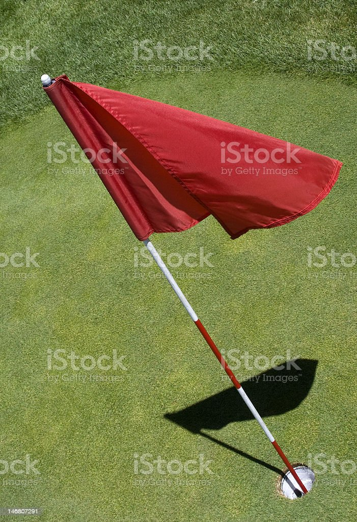 Red golf flag on a miniature golf course, flag has slight metallic...