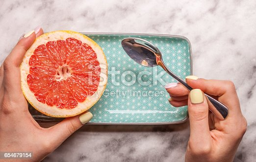 red cut grapefruit blue rectangular plate on white marble background
