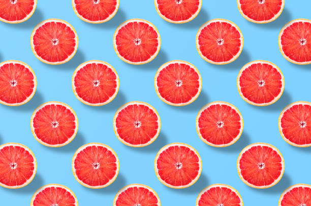 Red grapefruit slice pattern on colorful background stock photo