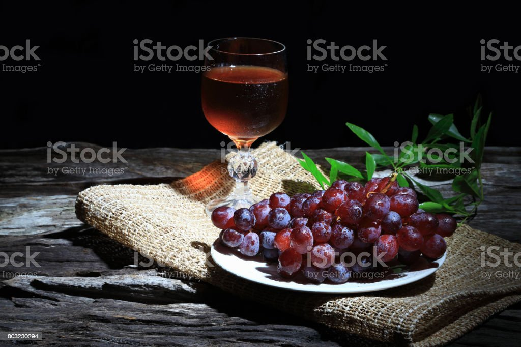 Red grapes and wine grapes on wooden board background, Dark tone. stock photo