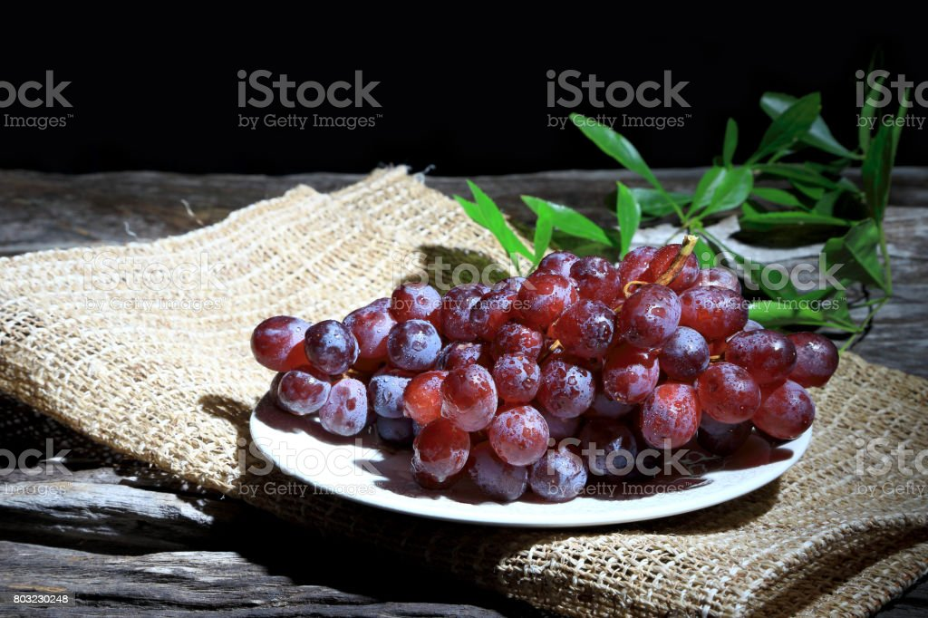 Red grapes on wooden board background, Dark tone. stock photo