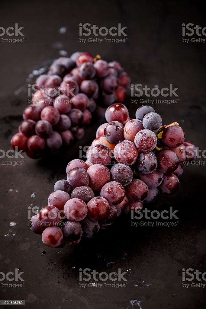 red grapes on wooden table stock photo