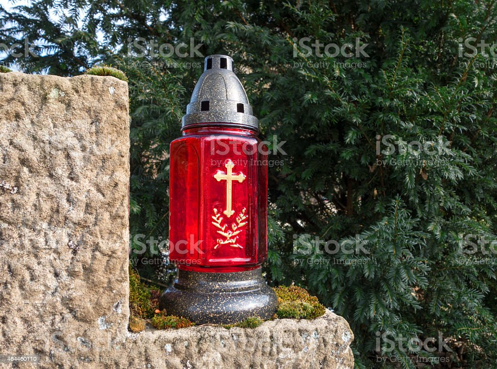 Red grave lantern with golden cross stock photo