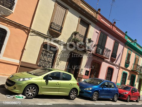 Valencia, Spain - June 26, 2020: Three colorful cars parked in the street. A lot of compact cars are moving around the city to avoid traffic issues