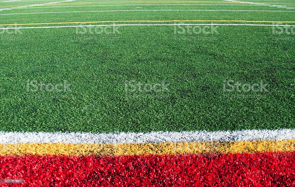 Red, green, yellow artificial turf playing field stock photo