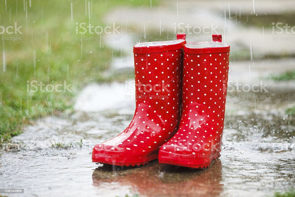 Red gumboots in rain stock photo