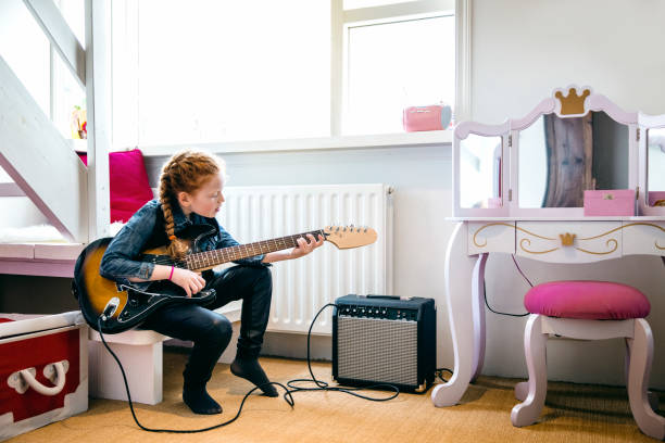 Red hair girl playing electric guitar in her bedroom. 8-9 year old caucasian girl playing and rocking with electric guitar in girls bedroom with princess mirror. Female child is wearing leather pants while playing instrument. girl bedroom stock pictures, royalty-free photos & images