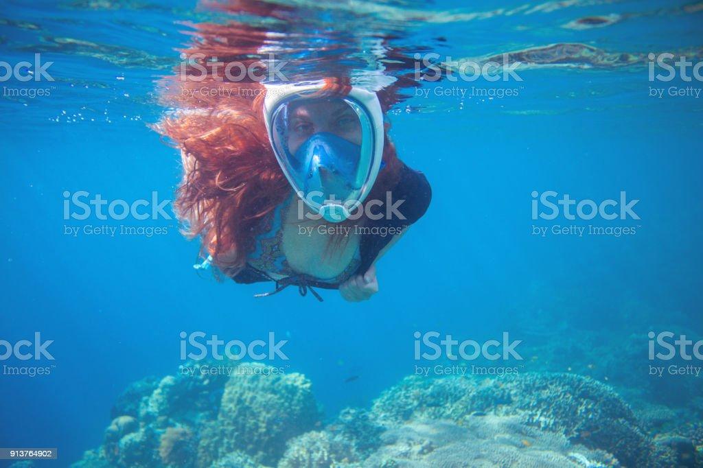 f97d1e284 Menina de cabelo vermelho debaixo d água no mar tropical. Snorkel em máscara  facial