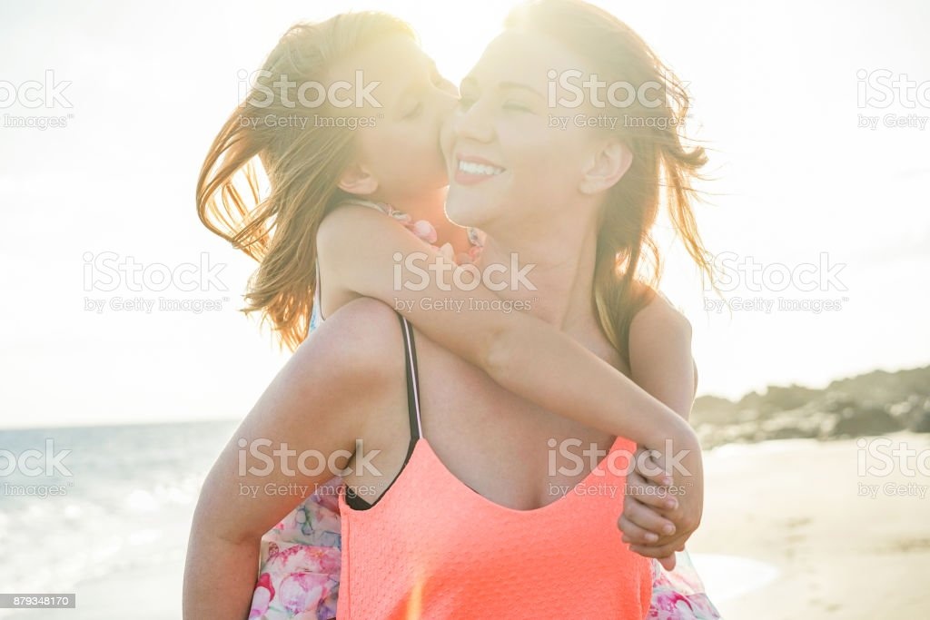 Red hair mother and daughter having fun on the beach - Mother enjoying time with her kid - Family lifestyle and love concept - Sun color tones filter - Focus on faces stock photo