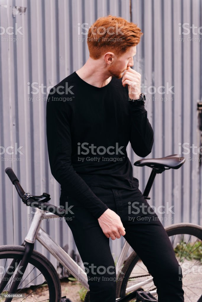Red hair young man sitting on his bicycle stock photo