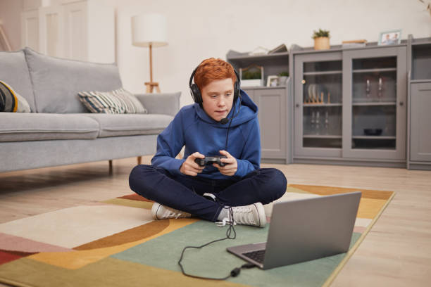 Red Haired Boy Playing Video Games on Floor stock photo