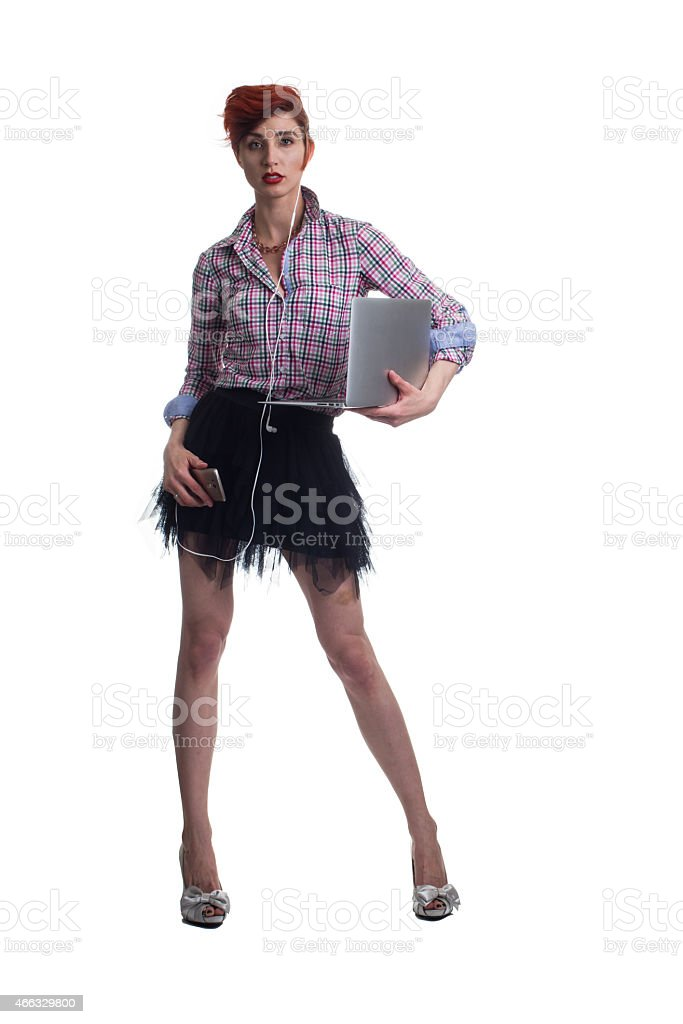 Red haired business woman carries laptop and holds smart phone stock photo