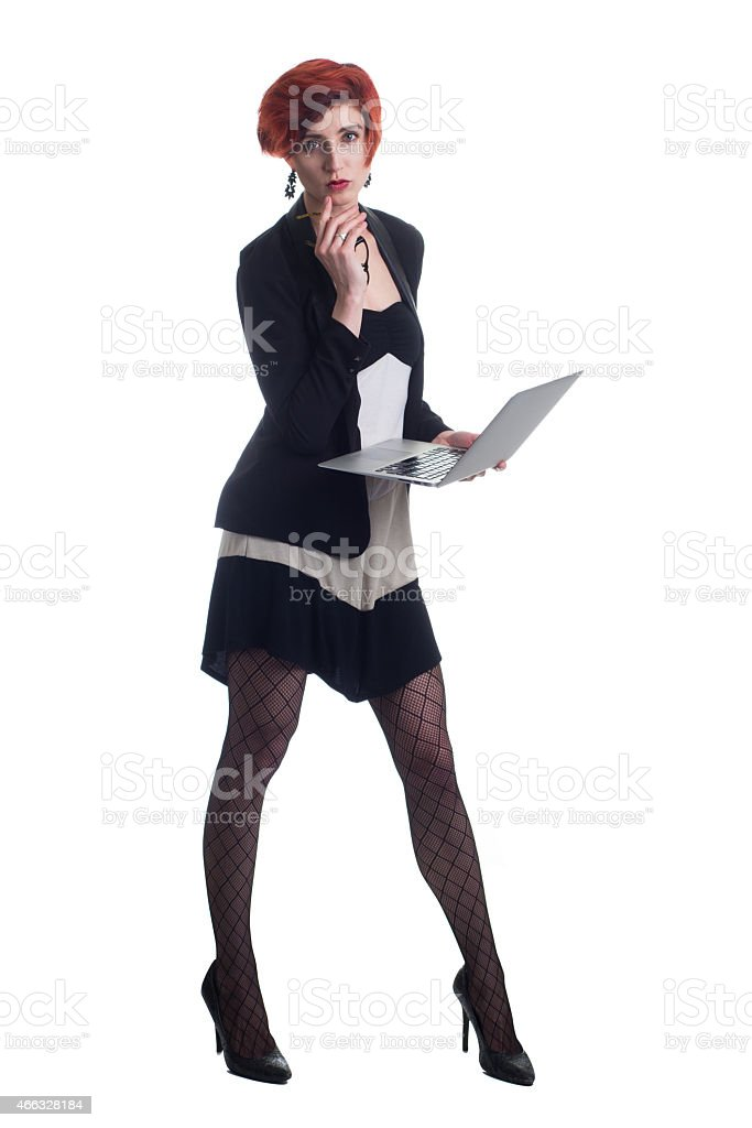 Red haired business woman checks laptop wearing heels and blazer stock photo