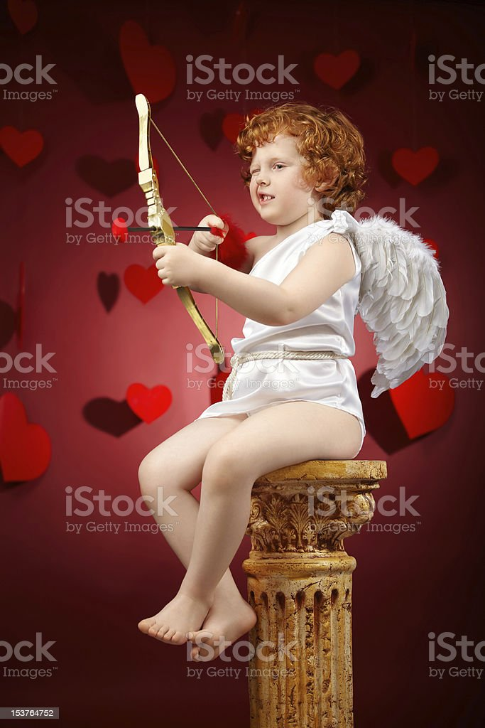 A red haired child dressed as an angel aiming with a bow stock photo
