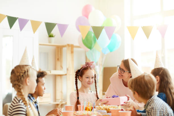 Red Haired Girl at Birthday Party Multi ethnic group of children celebrating birthday sitting at table in cafe, focus on happy red haired girl, copy space group of friends giving gifts to the birthday girl stock pictures, royalty-free photos & images