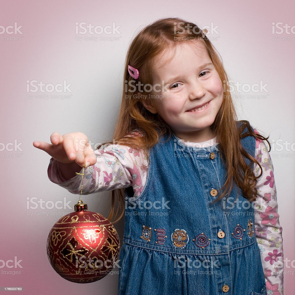 """Red haired girl holding a piece of decoration """"Little girl holding a piece of Christmas decoration, threatening to drop it..."""" Cheerful Stock Photo"""