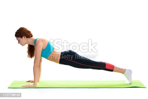 Red Haired Girl Is Doing Push Ups On Gym Carpet. Healthy Lifestyle. Fitness Club. Sporty Woman. Active Leisure. Body Shape. Keep Calm. Young And Beautiful. Repeat Exercises. Female Strength.