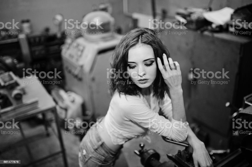 Red haired girl wear on short denim shorts and white blouse posed at industrial machine at the factory stock photo