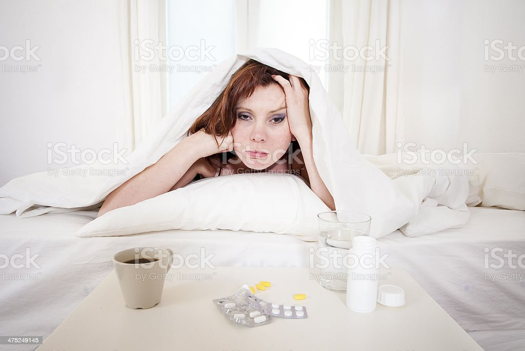 red haired girl with hangover wanting coffee in bed stock photo