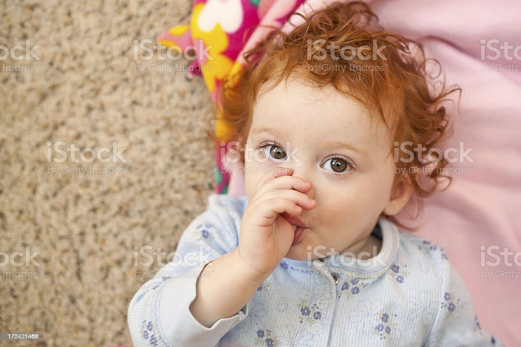 Red Haired Little Girl Laying on Floor Sucking Thumb royalty-free stock photo