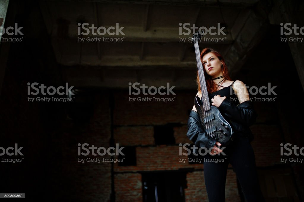 Red haired punk girl wear on black with bass guitar at abadoned place. Portrait of gothic woman musician. stock photo