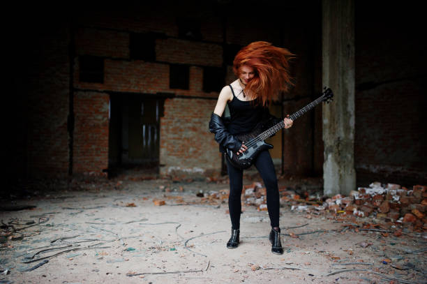 red haired punk girl wear on black with bass guitar at abadoned place. portrait of gothic woman musician. - punk music stock photos and pictures