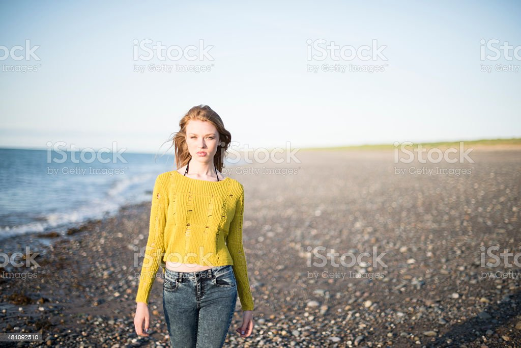 Red haired woman by the sea stock photo