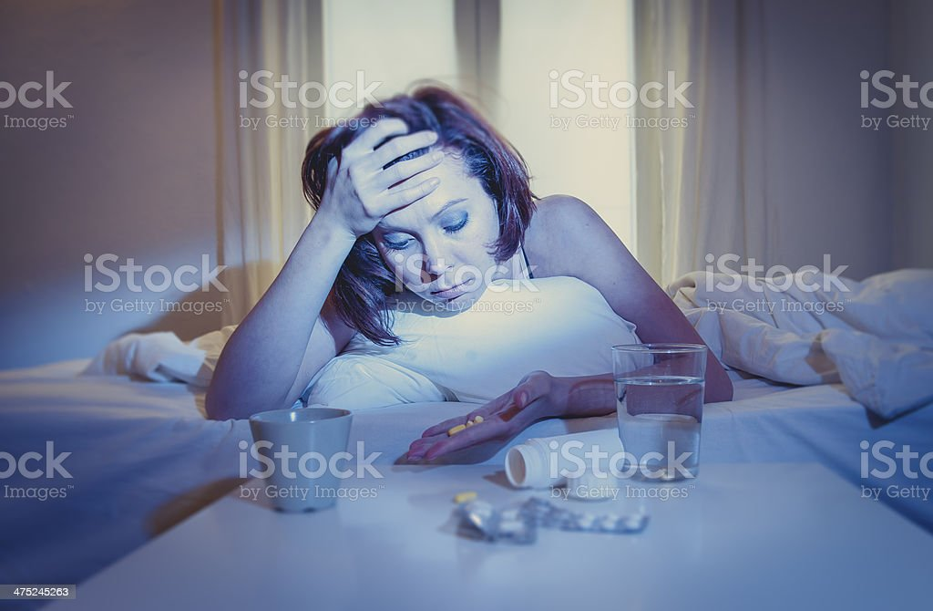 red haired woman sick in bed with medicine royalty-free stock photo