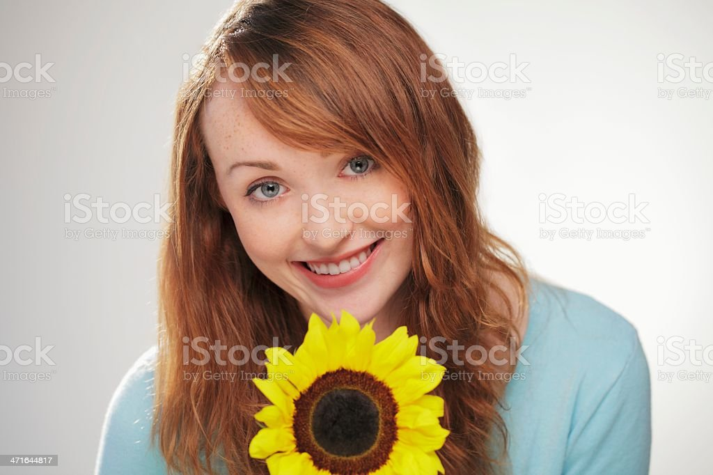 Red haired woman smiling with sunflower royalty-free stock photo