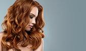 膨大な光沢のあると巻き毛の髪型と赤い髪の女性。髪を飛んでいます。