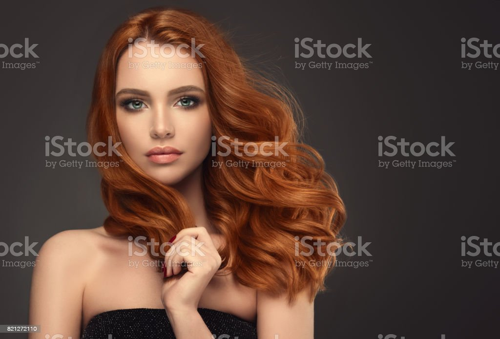 Red haired woman with voluminous, shiny and curly hairstyle.Flying hair. stock photo