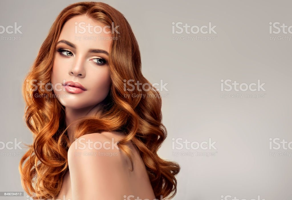 Red haired woman with voluminous, shiny and curly hairstyle.Flying hair. - foto stock