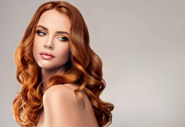 red haired woman with voluminous, shiny and curly hairstyle.flying hair. - makeup fashion stock pictures, royalty-free photos & images