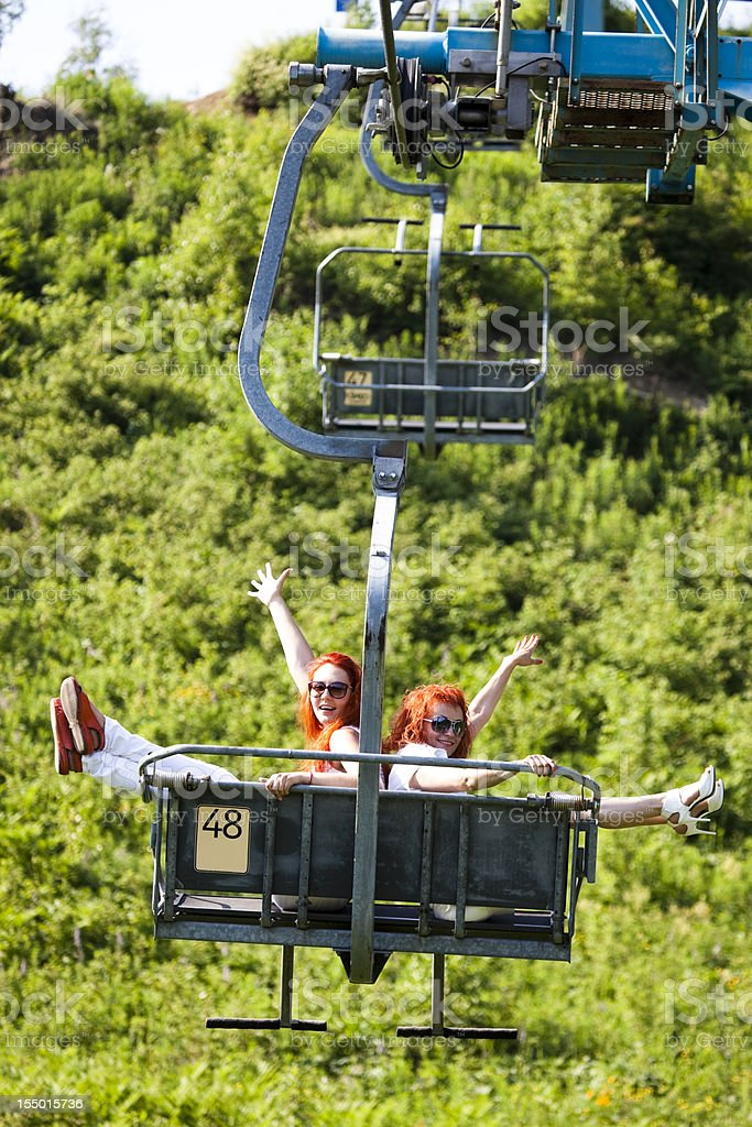 Red haired women ride  cableway royalty-free stock photo