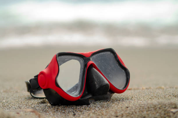 Red half diving scuba mask on beach sand,close up.Recreational sport hobby cover banner stock photo