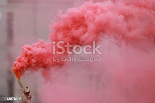 A man holding a hand flare with red smoke.