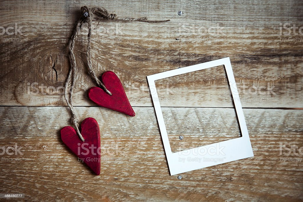 red handmade hearts with polaroid frame over old wooden background stock photo