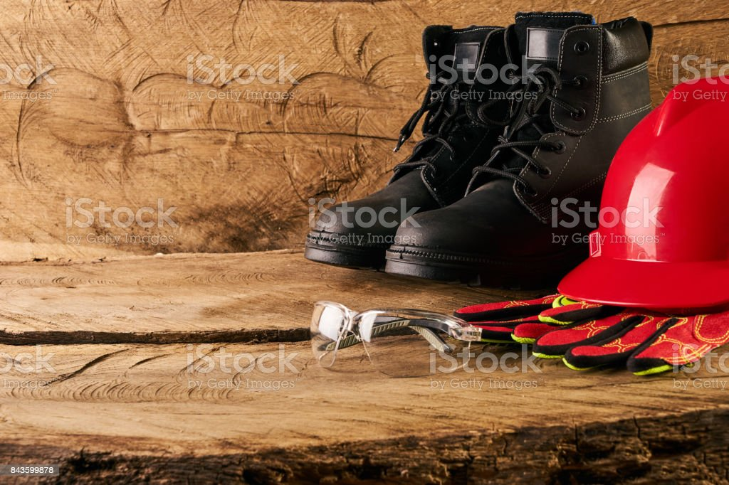 Red hard hat, gloves, protective glasses and safety boots stock photo