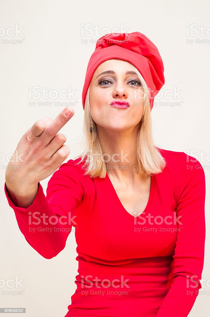 Red hat, blonde woman showing obscene gesture, middle finger stock photo