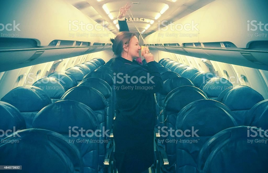 Red Head Flight Attendant Stewardess Demonstrating Oxygen Mask on Plane stock photo