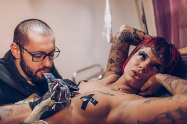 roten kopf auf dem bett mit schmerzen - tattoo ideen stock-fotos und bilder