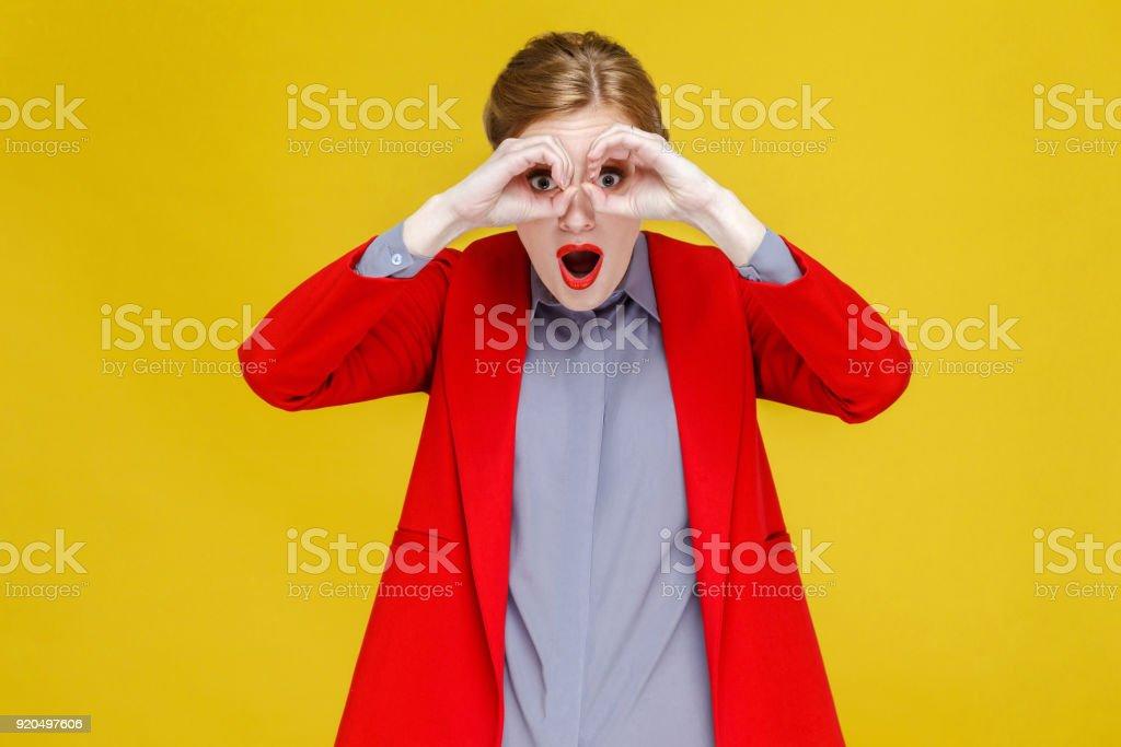 Red head woman in red suit looking in binoculars far far away. royalty-free stock photo